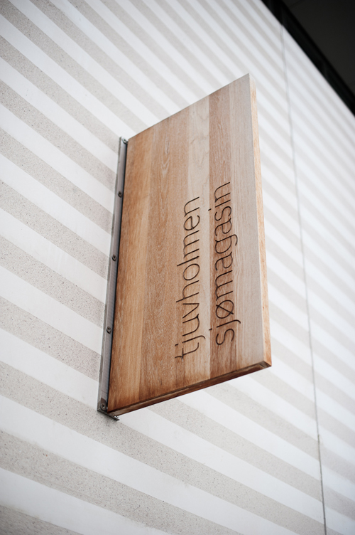 Træskilt i den nye bydel. Velkommen til tjuvholmen sjømagasin. Og til Linie Award 2011.