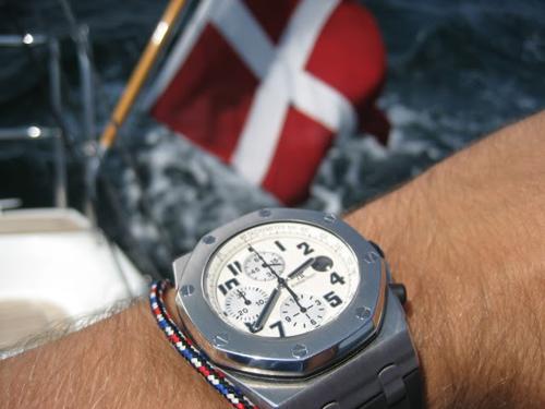 Skønt foto - bølgebrus, Dannebrog, et lækkert ur og noget snorværk om håndleddet.