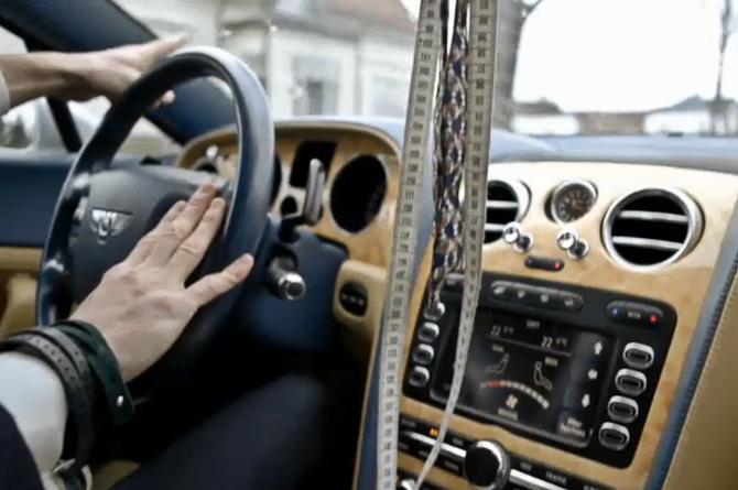 En mand, hans Bentley, målebånd og bow tie.