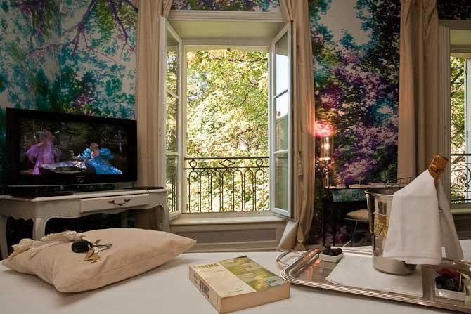 Junior suiten Vegetable er indrettet med 60'er møbler, skovprint på væggene og store vinduer, hvorfra sollyset strømmer ind.