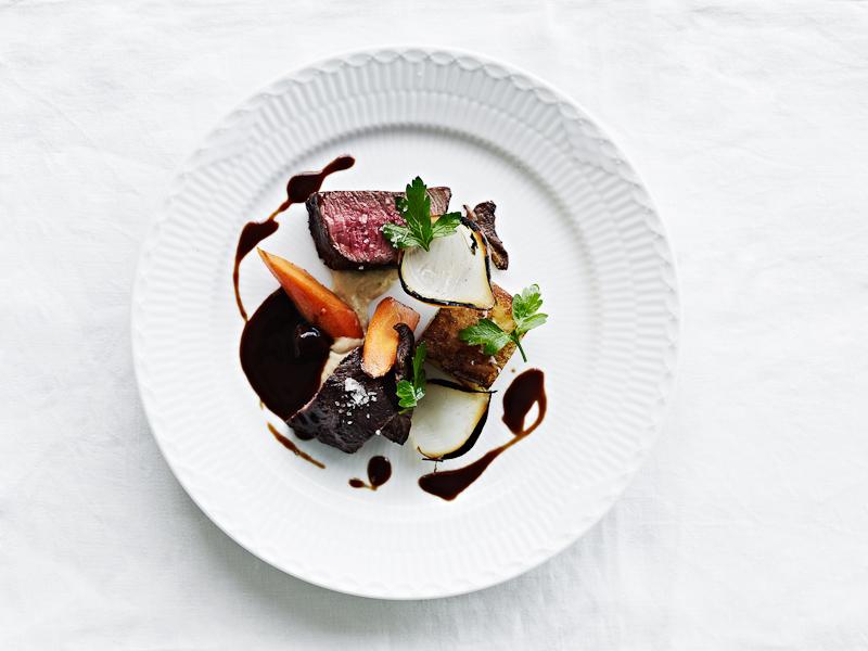 Oksetournedos fra Himmerland Syltede, brændte løg og løgkompot med persille og løvstikke Glaserede gulerødder og smørbagte kartofler Karl Johan svampesauce med hyldebæreddike