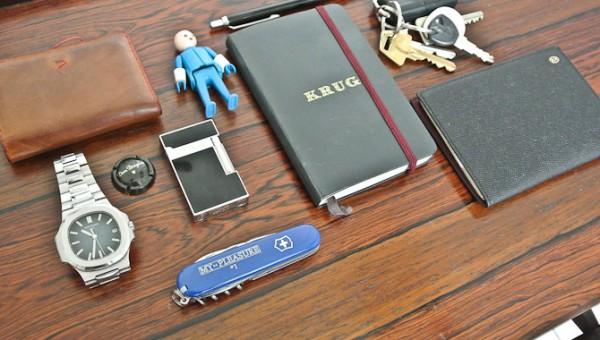 En pung, et ur, lillebror, en notesbog, en pen, mit pas, nøgler, lighter, en champagne kapsel og schweizer-frækkerten