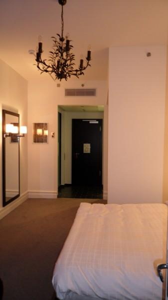 Nyredt seng, lysekrone anno dags dato og kig mod badet til venstre. WC på højre side.